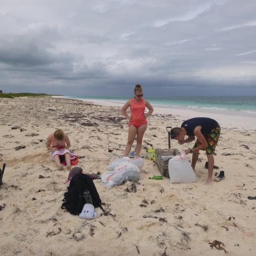 Students cleaning up trash on a beach in the Bahamas