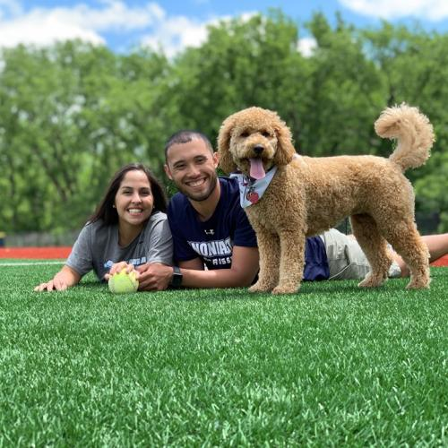 Justin and Jess laying on the OCC Softball Turf with their Dog