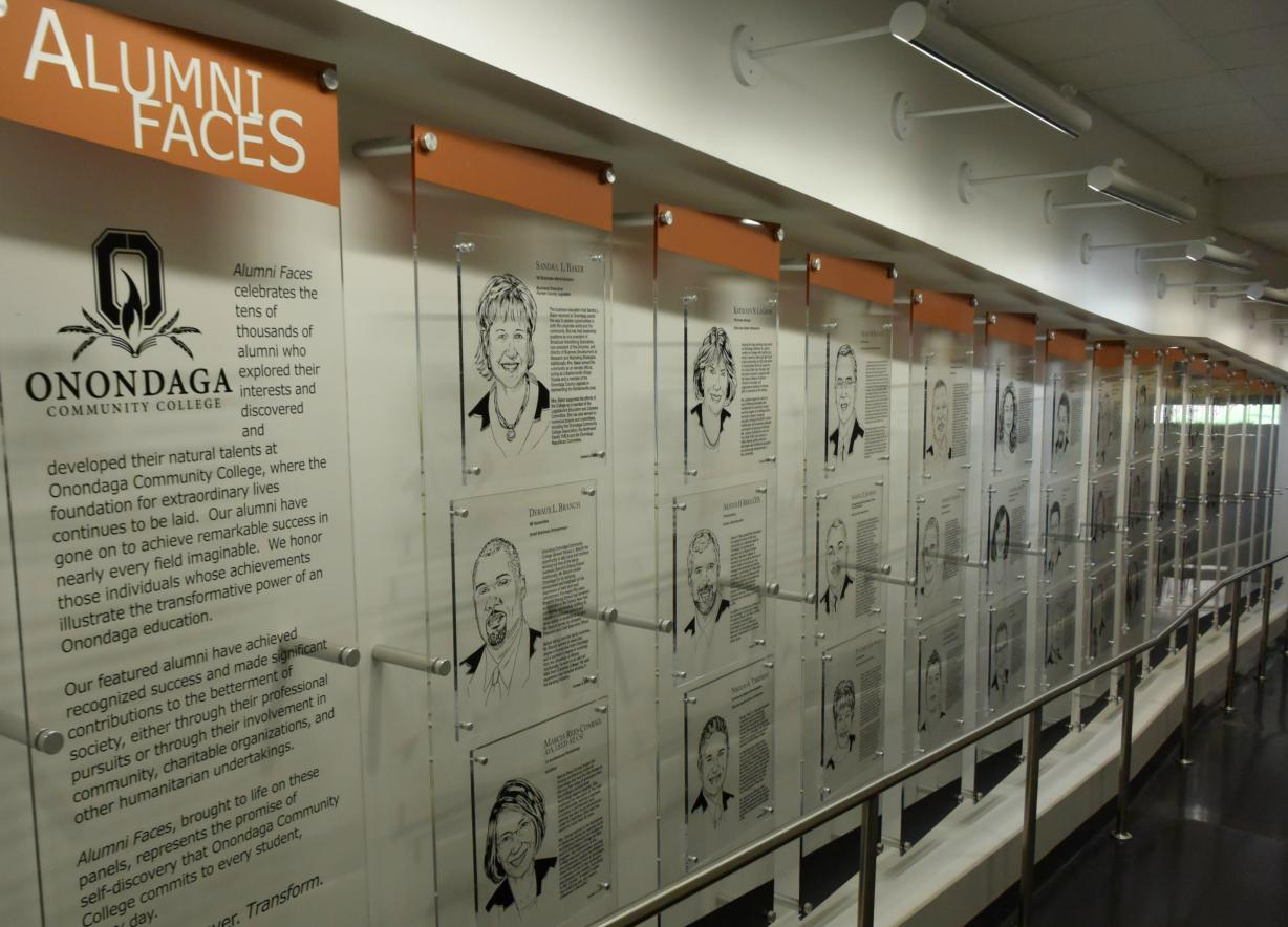 Photo of Alumni Faces etchings in the halls of the Academic II building.