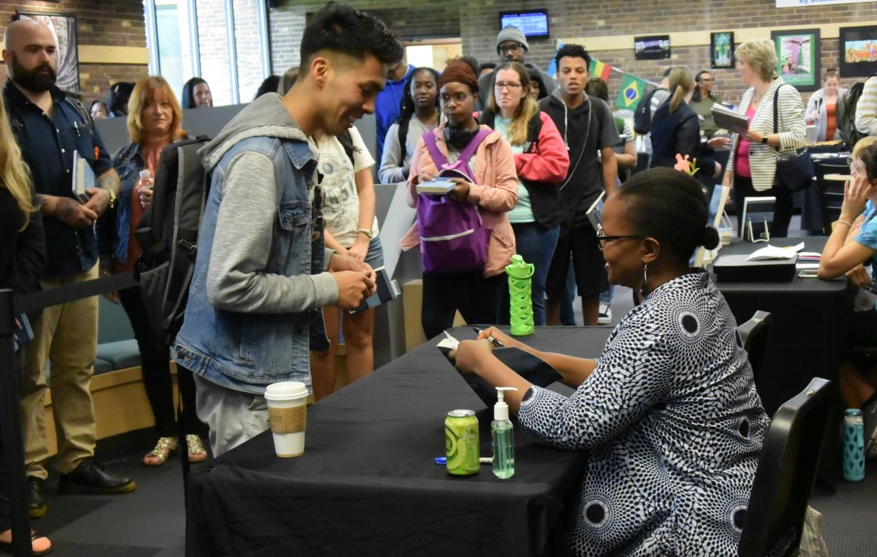 photo of students getting their book autographed by Edwidge Danticat