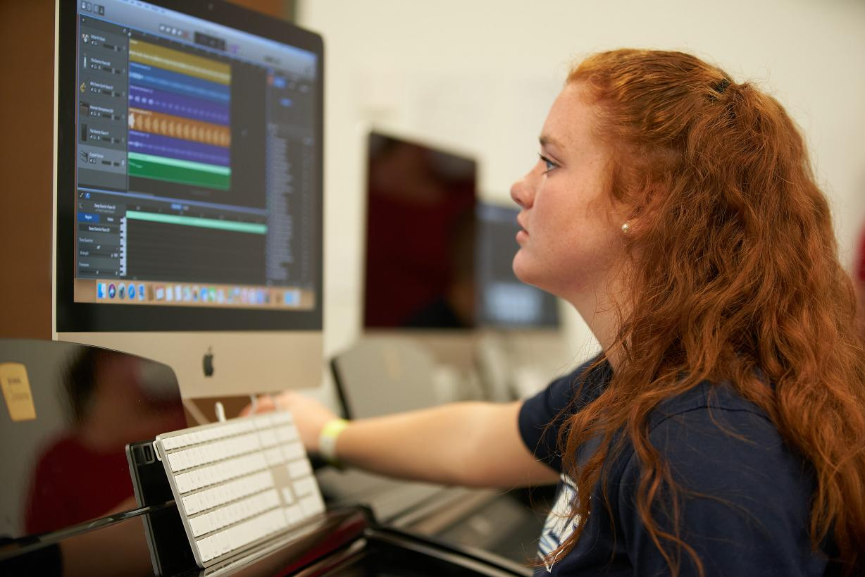 Female Student sitting at a computer with audio editing software displayed on the screen
