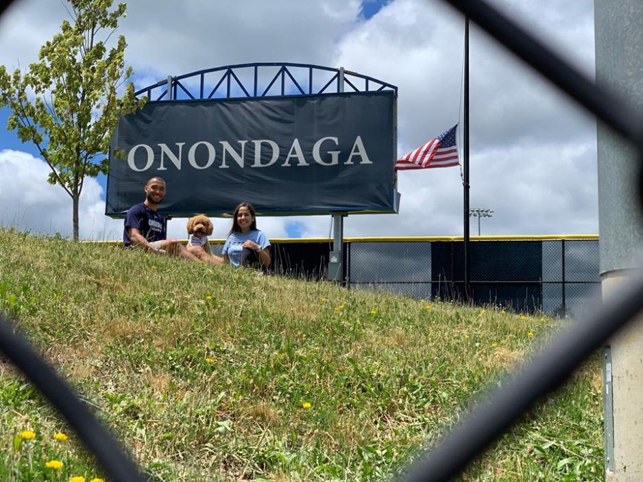 Justin and Jess with their dog and an Onondaga Sign in the background