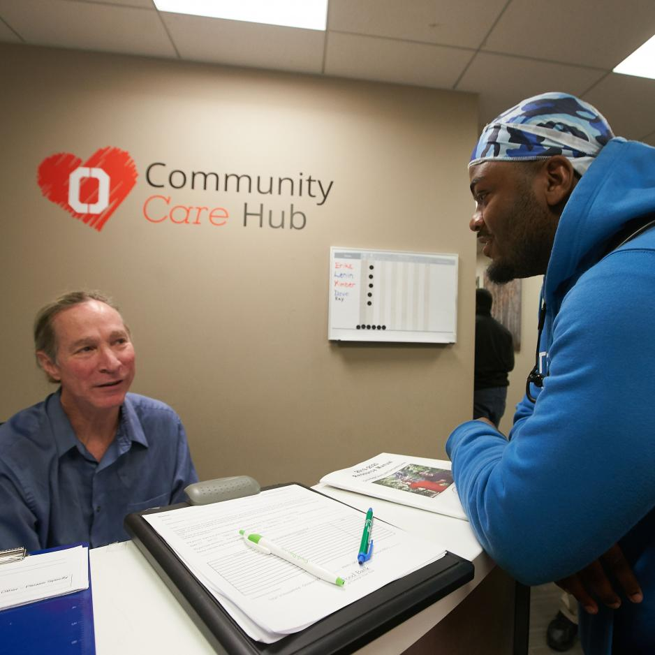 Student talking with a staff member at the Community Care Hub with the logo in the background