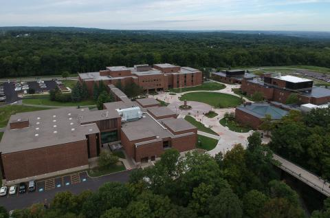 Aerial Shot of OCc's West Campus which includes three brown building and a clock tower