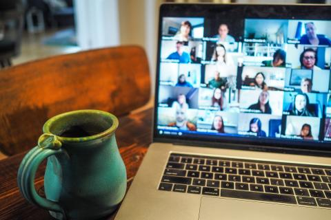 A Laptop opened to a Zoom Meeting with a Cup of Coffee Immediately Adjacent