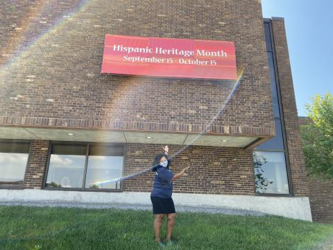 "Woman with a mask standing in front of a sign that reads ""Celebrating Latinx Heritage Month September 15 - October 15"""