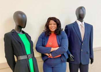 Woman of middle age in a red blouse and blue blaze standing in between and male and female mannequin in profession dress. Man is wearing a blue suite, woman is wearing a black blazer with a green dress.